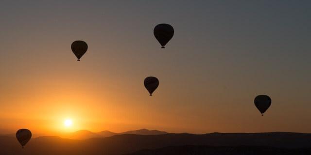 Varios globos volando en un atardecer.