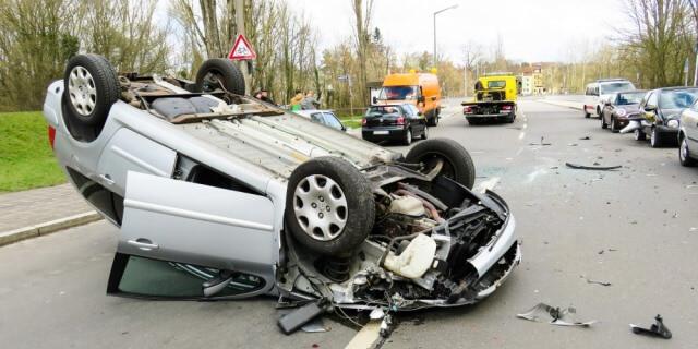 accidente de tráfico por colisión de vehículos (coche volcado en la carretera)