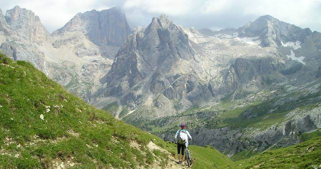 Ciclista en ruta contemplando un bonito paisaje de montaña.