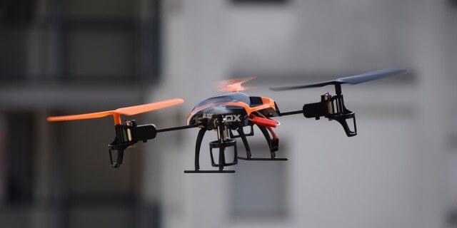 Dron naranja volando en una zona urbana.