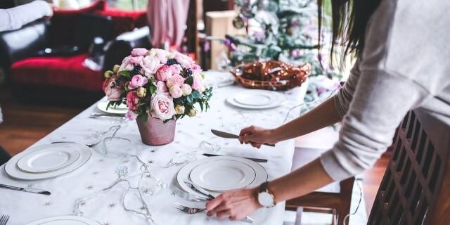 Mujer preparando la mesa de Navidad en su casa.