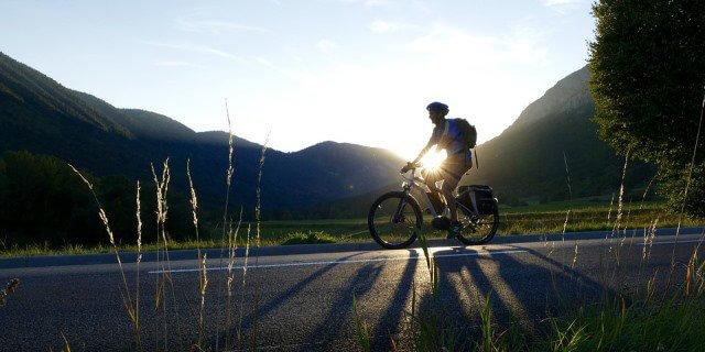 Ciclista montado en una bicicleta eléctrica, mientras cae el sol.
