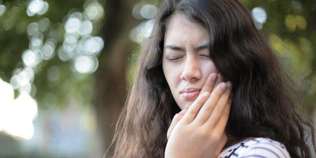 chica con dolor de muelas buscando remedios