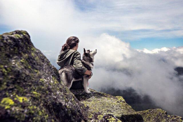 Chica descansa junto a su perro tras hacer senderismo