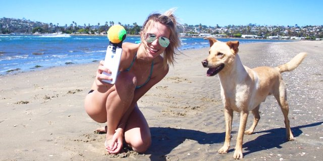 chica haciendo selfie con su perro mirando a cámara y quieto en la playa