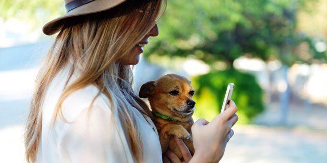 chica con el móvil junto a un perro