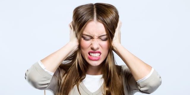 Chica joven tapándose los oídos por la molestia que le causa el ruido del tráfico rodado del exterior en la ciudad