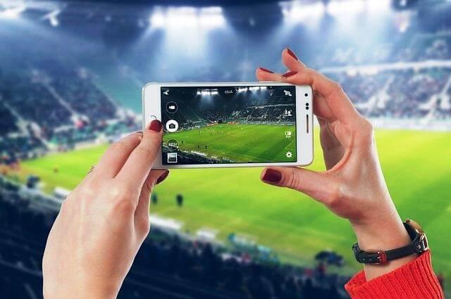 Espectadora hace una foto con su móvil en un partido.