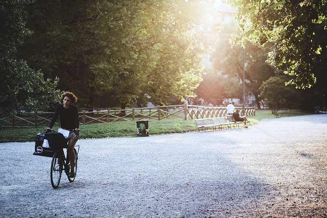 Chica pasea en bicicleta por un parque.