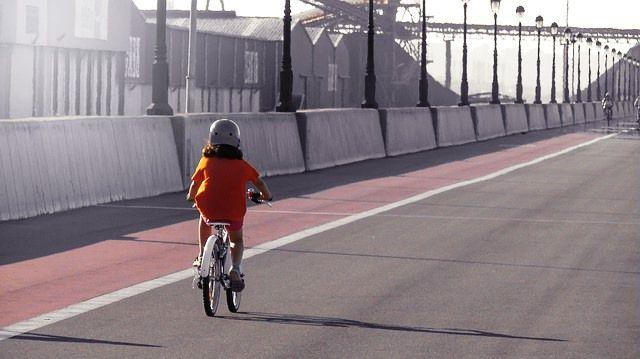 Chica monta en bici al lado del carril.