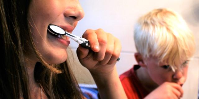 Niños cepillándose los dientes después de tomar un jarabe