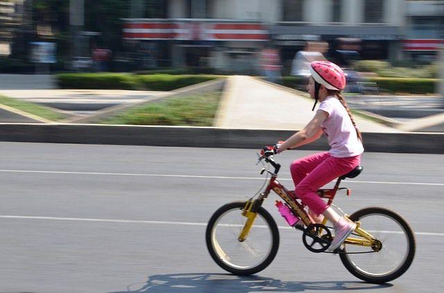 Chica circula con una bicicleta en ciudad.