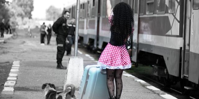 chica y perro esperan al tren